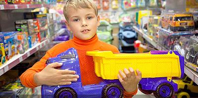 Un niño en una jugueteria sostiene un camion de juguete