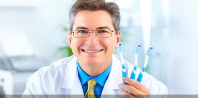 Dentista sonrriendo con sepillos de dientes en sus manos